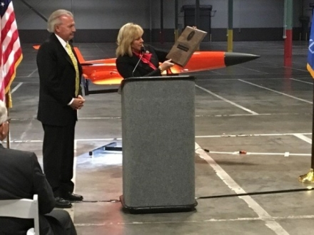 Governor Mary Fallin reads from a plaque she presented Friday to Eric DeMarco, president and chief executive officer of Kratos Defense & Security Solutions, Inc., during a ribbon-cutting ceremony at the company's new 100,000-square-foot unmanned aircraft production facility in the Will Rogers Business Park in Oklahoma City.