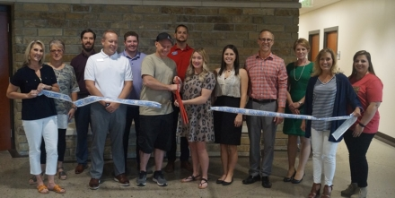 CJ and Raneka Covey cut the ribbon for their business River Valley Media. They are joined by members of the community and the Poteau Chamber of Commerce Board members