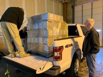 ODOC Director Scott Crow (at right) monitors while agency staff load up protective masks at an Oklahoma State Department of Health warehouse on Saturday, April 4, 2020. The masks went out to all correctional facilities in Oklahoma on Saturday to help keep correctional staff and inmates safe from COVID-19.